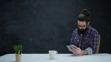 4K Portrait of smiling hipster man using computer tablet on chalkboard background