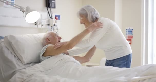 4K Senior man in hospital room, wife and daughter visiting and chatting with him