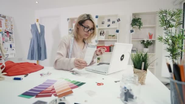 4K Fashion designer working at her desk in creative studio