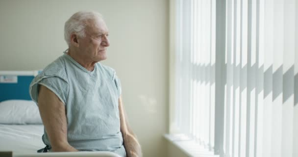 4K Portrait of smiling elderly patient sitting on his bed in hospital room