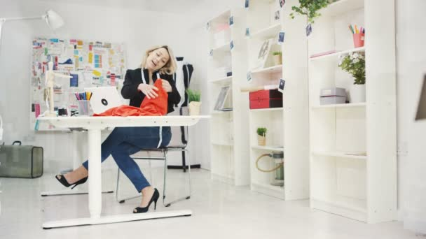 4K Fashion designer in her studio, working on laptop and talking on phone