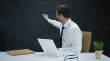 4K Businessman with laptop moving his hand as if writing or drawing on chalkboard