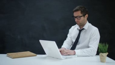 4K Pensive businessman working on laptop with chalkboard background