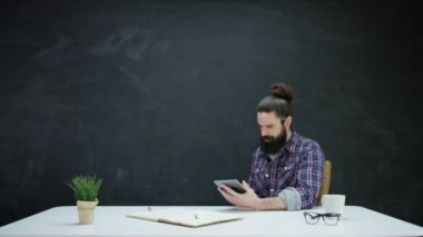 4K Hipster man working on tablet and looking at chalkboard behind for inspiration