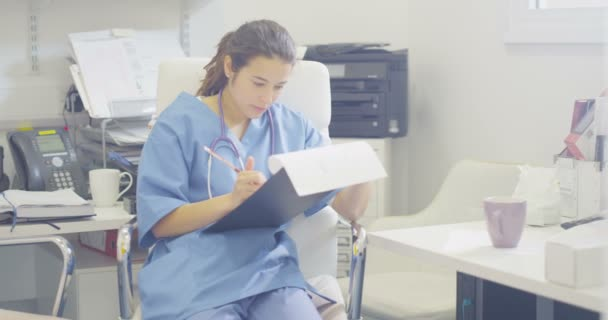 4K Medical worker alone in office writing notes on patient medical record