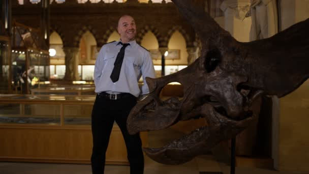 4K Portrait of funny security guard standing next to dinosaur skeleton in museum