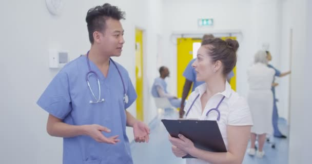 4K Cheerful colleagues in modern hospital chatting in busy hallway