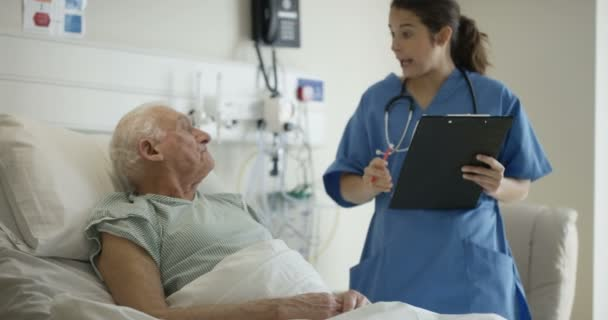 4K Caring medical worker in hospital talking to elderly man at his bedside