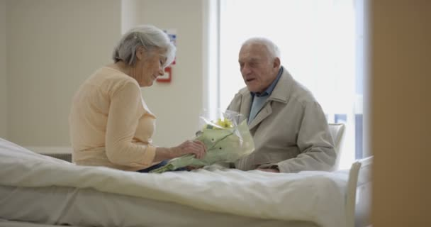 4K Senior couple in hospital room, man visiting his sick wife and giving flowers.