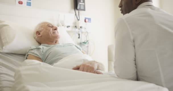4K Friendly doctor comforting elderly patient at his bedside