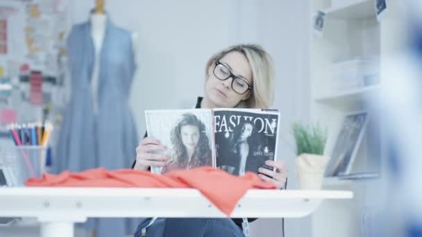 4K Smiling dressmaker in her studio, looking at magazine for inspiration