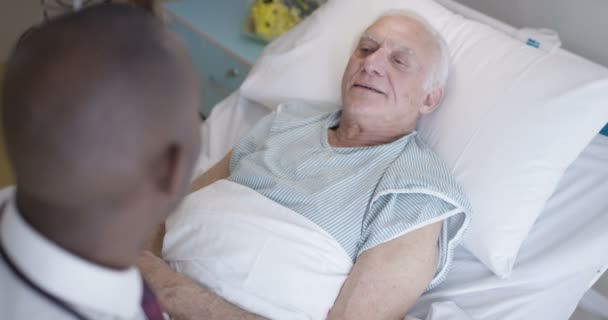 4K Friendly doctor talking to elderly patient at his bedside