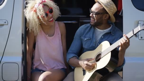 4K Happy hipster couple on road trip singing and playing guitar in camper van