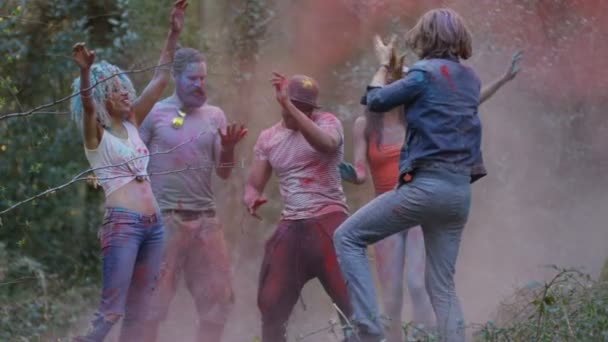 4K Happy hipster friends at music festival, dancing and throwing coloured powder.