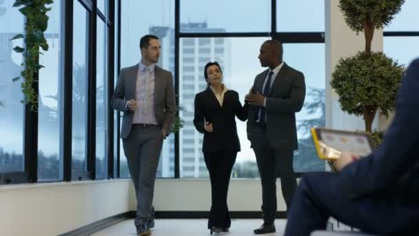 4K Mixed ethnicity corporate business group chatting as they walking through office