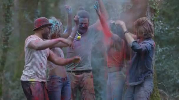 4K Portrait of smiling friends covered in coloured powder at festival