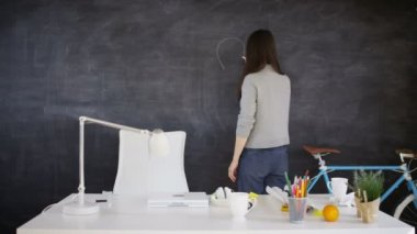 4K Woman drawing light bulb on blackboard, education or creative office concept
