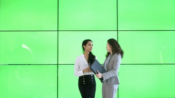 4K Businesswomen having a discussion on modern green screen background