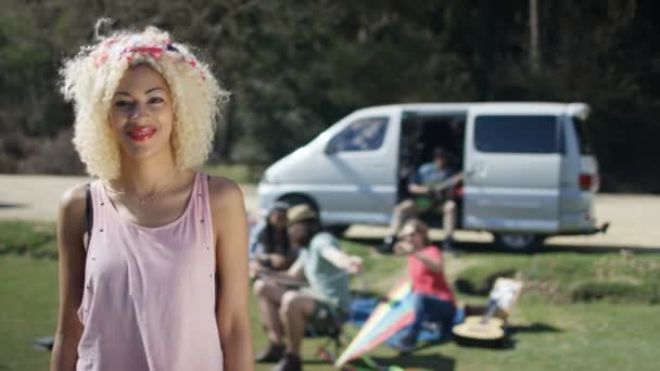 4K Portrait of smiling hipster girl with friends at music festival campsite