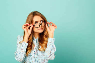 Pretty thoughtful girl wearing glasses over blue background