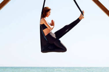 young beautiful brunette woman doing fly yoga. Sitting in hammoc
