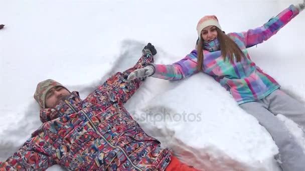 Mladý pár ležet ve sněhu takže Snow Angels. Zpomalený pohyb