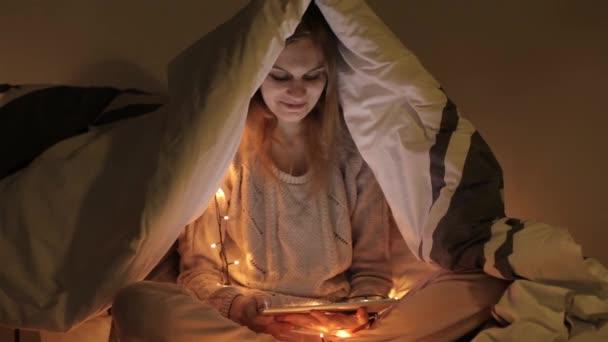 Gyönyörű lány, egy tabletta ül egy ágy, egy mesebeli fények egy takaró alatt