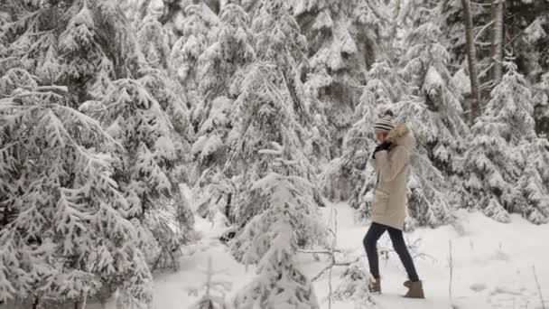 Dívka chodí v zasněženém lese zimní