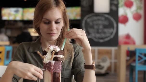 Krásná dívka v Cafe pije mléko koktejl