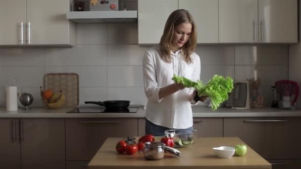 Obchodní žena připravuje večeře v kuchyni připravuje vegetariánský salát. Trhání salát