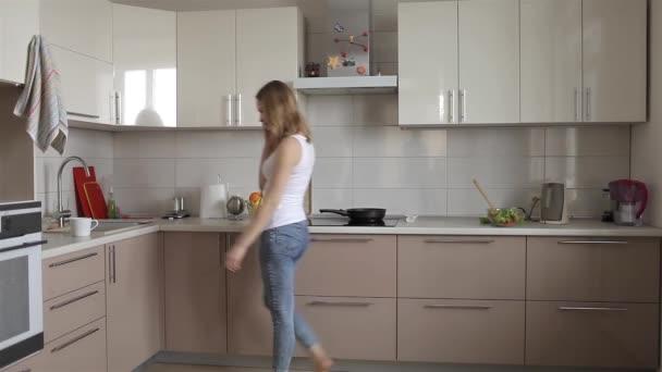 Krásná dívka mluví po telefonu a chodit do kuchyně