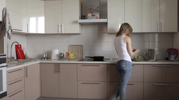 Štíhlá dívka připravuje jídlo, salát v kuchyni
