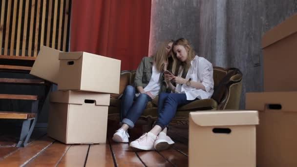 Dvě dívky soused se pohybují, sedící na gauči mezi bednami s telefonem