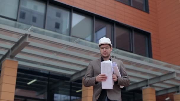 Architect, Businessman Looking at Blueprints on the Background of an Architectural Building