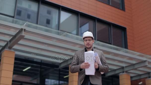 Architekt, podnikatel, při pohledu na plány na pozadí architektonické budovy