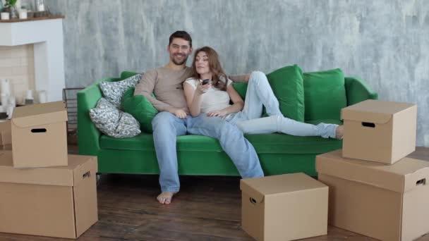 Boldog pár néz tv feküdt a díványon, költöztető dobozok