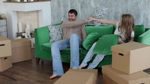 Happy Couple Fighting by Cushions, Boxes Moving to New Apartment