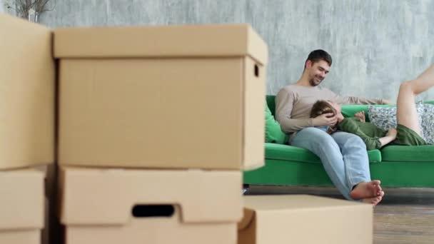 Umzugskartons und das glückliche junge Paar ruht sich auf der Couch aus