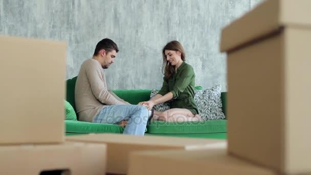 Šťastný pár házení Popcorn sedí na pohovce mezi boxy, stěhování
