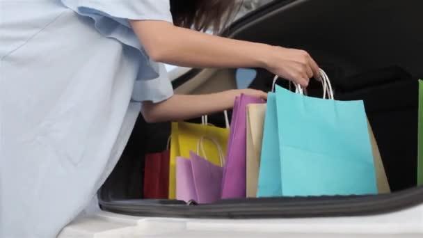 Dívka Shopaholic piloty nákupní tašky v kufru auta