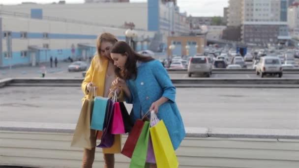 Dva šťastná dívka s nákupní tašky hodinky nákupy poblíž nákupního centra