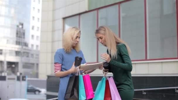 Vidám barátnője egy csomó vásárlás csomagok mutatja ki vásárlás, állt az utcán