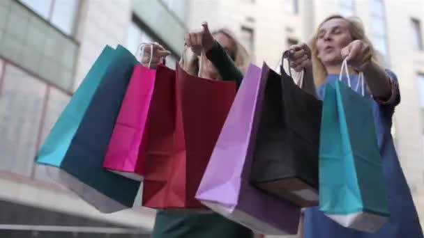 Detail, dvě dívky drží spoustu nákupních tašek na ulici