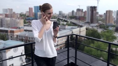 Beautiful Business Woman Talking on the Phone Standing on the Roof Overlooking the City