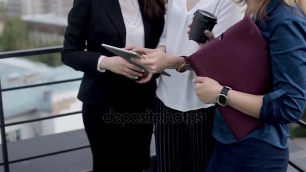 Business-Konferenz auf dem Dach. drei Geschäftsfrauen diskutieren über die Arbeit mit einem Tablet auf dem Dach über der Stadt