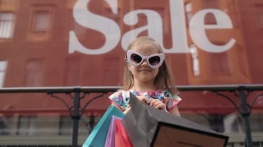 A Little Girl With Shopping Bags at a Showcase With an Inscription Sale