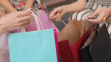 Little Girl Looks in Bags With Purchases From Mom