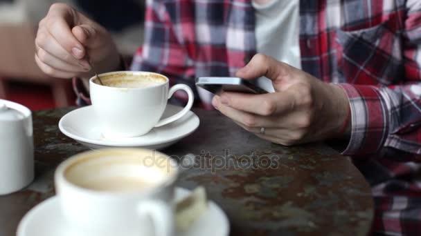 Az ember használ mozgatható telefon, a kávéház. Közeli kép:
