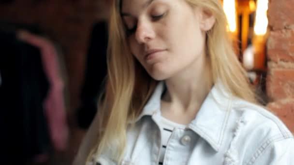Krásná žena používá telefon, zatímco sedí v Cafe