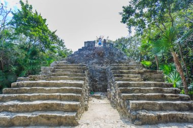Kid standing on the top of antique ruins